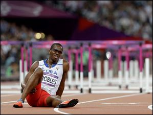 Cuba's Dayron Robles sits on the track after injuring his leg in the men's 110-meter hurdles final.