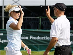 Golfer Natalie Gulbis congratulates playing partner Brad Stirling after he made a putt.