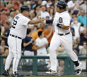 Detroit's Miguel Cabrera is congratulated by third base coach Gene Lamont after hitting a solo home run in the fourth inning.