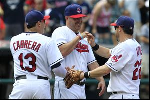 Cleveland Indians manager Manny Acta, center, smiles as he congratulates Asdrubal Cabrera, left, and Jason Kipnis after the Indians defeated the Minnesota Twins 6-2.
