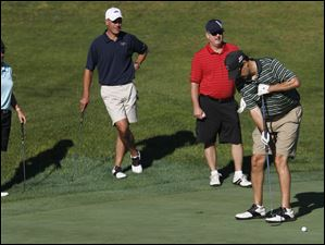 Pro golfer Reilley Rankin, David Clark and Brian Deszell watch Jeffrey Applebaum putt.