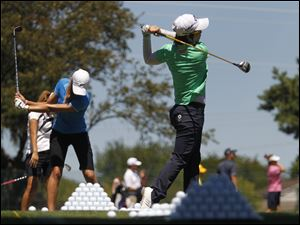 South Korean pro golfer Eun-Hee Ji, right, practices on the driving range.