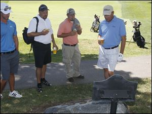 From left: Caddy Duane Smith, Bruce Vaandrager, of Huntington Bank, Tod Fox and Ben Wiers, of Huntington Bank, read the names of famous golfers mounted to a rock at the Inverness Club. The site is established as a National Register of Historic Places.