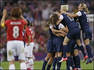 United States players celebrate today winning the women's soccer gold medal match as Japan's Aya Miyama, left, reacts at the 2012 Summer Olympics.