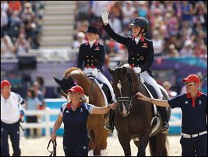 Gold medal winner Charlotte Dujardin of Great Britain waves as she arrives for the medal ceremony in the equestrian dressage individual competition.  In the background left teammate and bronze meal winner Laura Bechtolsheimer.