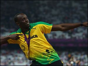 Gold medalist Usain Bolt of Jamaica celebrates during the medal ceremony for the Men's 200m.