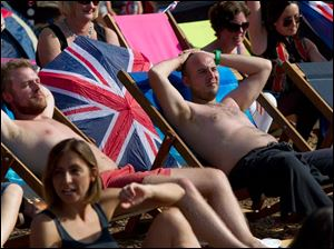 Fans of Britain's team sit on deck chairs while watching the Olympic Games on large screens, at the BT London Live concert.