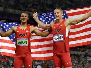 United States' gold medal winner Ashton Eaton, left, and his silver medalist teammate Trey Hardee, right, pose with their national flag after the men's decathlon.
