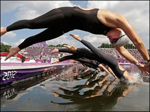 Germany's Angela Maurer, front, and other athletes dive into the Serpentine at Hyde Park as they compete in the women's marathon swimming competition.