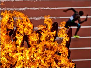 An athlete passes the Olympic flame during a men's 4 x 400-meter relay heat.