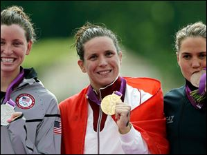 Gold medalist Eva Risztov of Hungary, center, stands with silver medalist Haley Anderson of the United States, left, and bronze medalist Martina Grimaldi of Italy during a medals ceremony after the women's 10-kilometer marathon swimming competition.