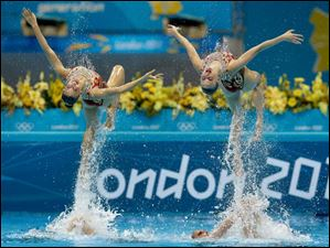 Members of the team of Russia are thrown up in the air during the women's team synchronized swimming technical routine.