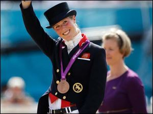 Laura Bechtolsheimer of Great Britain waves after receiving the bronze medal in the equestrian dressage individual competition.