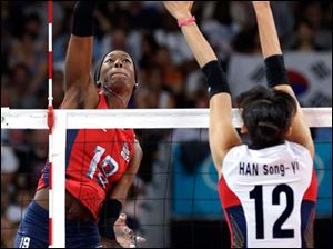 USA's Destinee Hooker (19) goes up for a smash in front of South Korea's Han Song-yi (12) during a women's volleyball semifinal match.