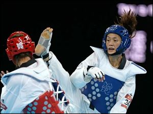 Chinese Taipei's Li-Cheng Tseng fights Britain's Jade Jones (in red) during their semifinal round match in women's 57-kg taekwondo.