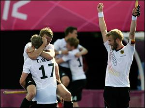 German players celebrate following their 4-2 win over Australia in their men's field hockey semifinal match.