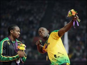 Silver medalist Yohan Blake (L) of Jamaica watches as Gold medalist Usain Bolt (R) of Jamaica celebrates on the podium during the medal ceremony for the Men's 200m.