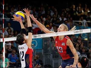 USA's Christa Harmotto (13) spikes the ball over South Korea's Han Song-yi (12) during a women's volleyball semifinal.