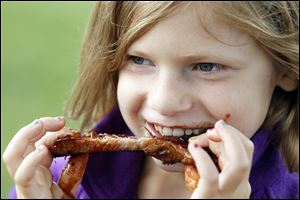 Zoe Edwards, 9, of Maumee  sinks her teeth into a rib at the 29th annual Northwest Ohio Rib-Off  at the Lucas County Fairgrounds.