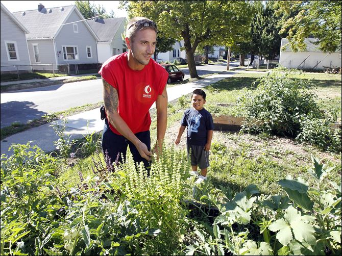 Brad Fields, an urban urban agriculture/landscape design student  Brad Fields, an urban urban agriculture/landscape design student at Owens Community College, left, and little helper Martine Garcia, 5, right, pulls out a few weeds from his tomato patch in a community garden in Toledo.