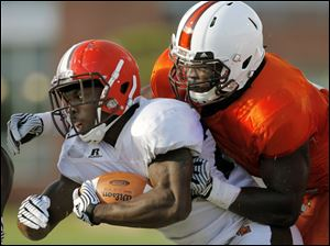 Bowling Green State University running back John Pettigrew (20) runs the ball against BGSU defender D.J. Lynch during a scrimmage Saturday.