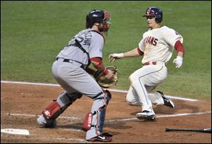 Cleveland Indians' Brent Lillibridge, right, scores around Boston Red Sox catcher Jarrod Saltalamacchia on a suicide squeeze bunt in the seventh inning of a baseball game on Saturday.