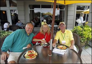 Bob Hodak, left, Mary Thomas, center, and Ed Grabowski, right, enjoy the patio of the clubhouse during the Jamie Farr at Highland Meadows Golf Club.