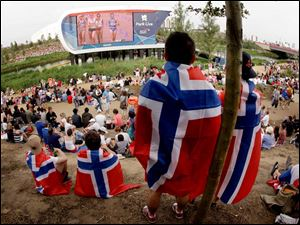 Visitors watch race walking on a big screen in Olympic Park at the 2012 Summer Olympics Saturday.