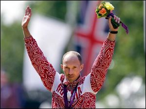 Gold-medallist Russia's Sergey Kirdyarkin acknowledges the crowd following the men's 50-kilometer race walk.