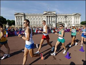 Athletes walk past Buckingham Palace as they compete in the men's 50-kilometer race walk.