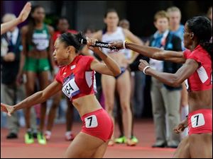 United States' DeeDee Trotter, second from right, hands the baton to United States' Allyson Felix as they compete to win gold in the women's 4x400-meter relay final during the athletics in the Olympic Stadium.