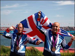 Great Britain's Liam Heath, right, and Jon Schofield celebrate at the podium after winning the bronze medal in the men's kayak double 200m in Eton Dorney, near Windsor, England.