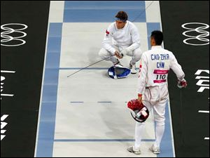 David Svoboda, left, of the Czech Republic waits to begin his bout with Cao Zhongrong of China during the men's fencing section of the modern pentathlon.