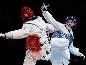 Russia's Gadzhi Umarov fights Canada's Francois Coulombe-Fortier (in red) during their match in men's plus 80-kg taekwondo competition.