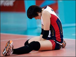 South Korea's Kim Yeon-koung sits on the court during a three set loss to Japan in the women's volleyball bronze medal match.