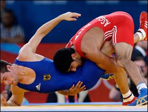 Toghrul Asgarov of Azerbaijan competes against Tim Schleicher of Germany (in blue) during the men's 60-kg freestyle wrestling competition.