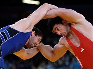 Zaurbek Sokhiev of Uzbekistan competes against Ibragim Aldatov of Ukraine (in blue) during the men's 84-kg freestyle wrestling competition.