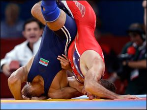 Coleman Scott of the United States competes against Toghrul Asgarov of Azerbaijan (in blue) during the men's 60-kg freestyle wrestling competition.