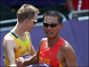 Tianfeng Si, of China, celebrates taking the bronze medal in the men's 50-kilometer race walk.