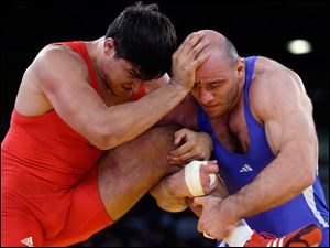 Nick Matuhin of Germany competes against Artur Taymazov of Ukbekistan (in blue) during the men's 120-kg freestyle wrestling competition.