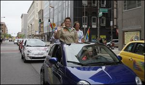 Jennifer Tyrrell, one of two grand marshals for the Toledo Pride parade, waves to the crowd as a rainbow of Fiat 500s travels forward.
