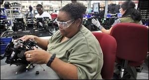 Awilda Isaac, left, works on a printer being assembled at Datacard Co. in Minnetonka, Minnesota. The company, which recently moved a production line from a plant in Malaysia to Minnetonka, is among several in the state that have moved manufacturing operations back to the States.