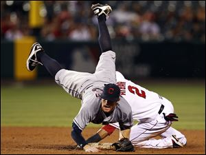 Cleveland Indians' second baseman Jason Donald is upended but completes the double play on Los Angeles Angels' Erick Aybar at second and Chris Iannetta at first in the fifth inning of Monday night's game in Anaheim, Calif.