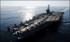 The Nimitz-class aircraft carrier USS John C. Stennis (CVN 74) transits the Straits of Hormuz on Nov. 12, 2011.