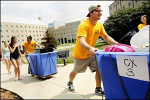 Logan Bowling, a first-year resident orientation guide, helps move a freshman into her dormitory at the University of Toledo. Rockets have until Sunday to pay their bills in full or make arrangements.