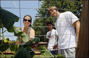 Meghan Yarnell picks a cucumber with Sammy Irias, center, and her husband, Andy Yarnell, in their backyard garden.