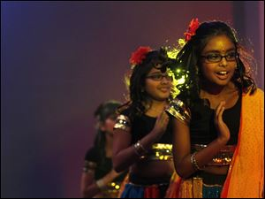 Anika Singhania, 11, of Sylvania, right, performs a Bollywood dance alongside eight other girls before a crowd of hundreds.