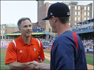 BGSU head football coach Dave Clawson shakes hands with Toledo Mud Hens pitcher Thad Weber after throwing out a first pitch before the Hens take on the Louisville Bats.