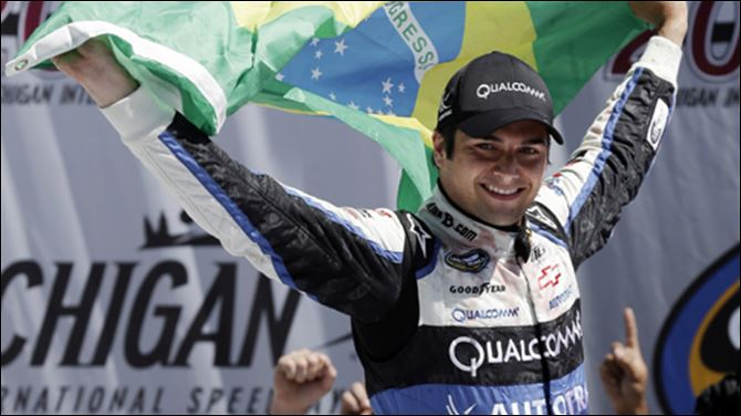 Nelson Piquet Jr., holds the Brazilian flag while celebrating in victory lane after winning the NASCAR Camping World Truck series VFW 200 at Michigan International Speedway.