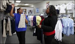 Evelyn Robinson, left, owner of School Matters, helps Aishah McLaughlin find school uniforms at her shop in the Great Eastern Shopping Center. Ms. Robinson moved her store from West Toledo this year.